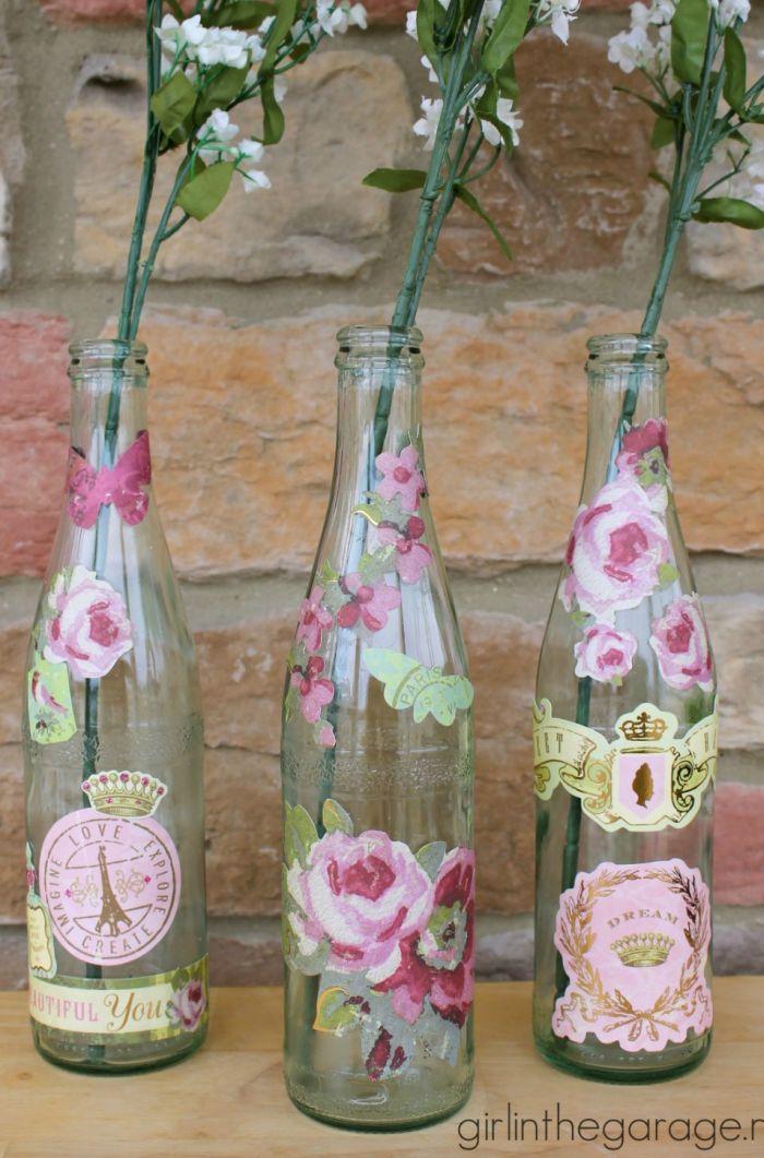 garrafa de vidro com flores coladas